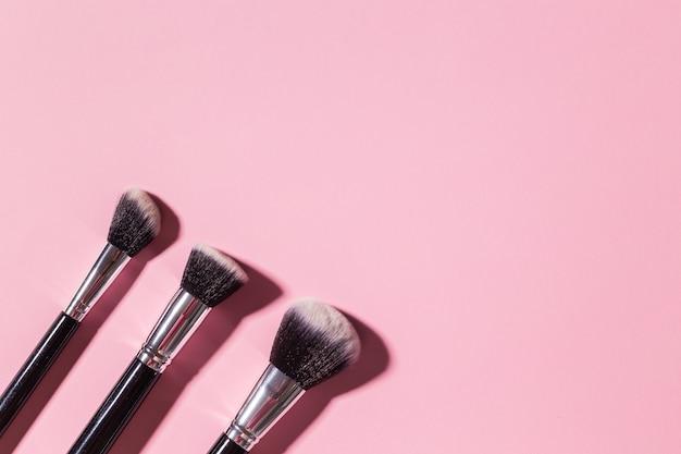 Różne pędzle do makijażu na różowym tle z kosmetycznym widokiem z góry i koncepcją urody