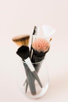 Różne pędzle kosmetyczne w przezroczystym szkle
