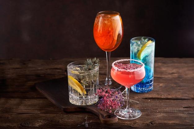 Różne piękne koktajle w ciepłych kolorach na ciemnym tle. koncepcja menu koktajlowego lub barowego.