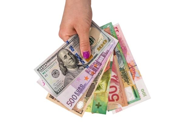 Różne pieniądze świata w kobiecej dłoni na białym tle