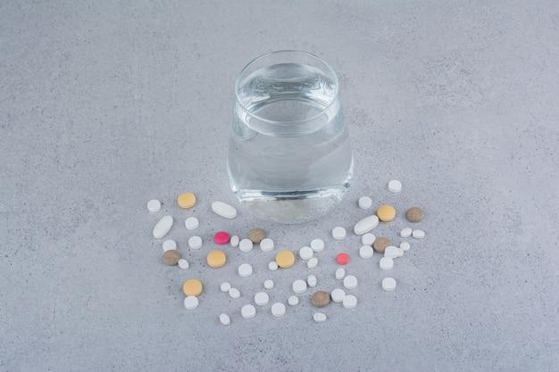 Różne pigułki medycyny farmaceutycznej i szklankę wody.