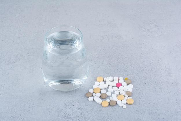Różne pigułki medycyny farmaceutycznej i szklankę wody