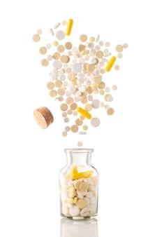 Różne pigułki wylatują ze szklanego słoika pigułek na białym tle