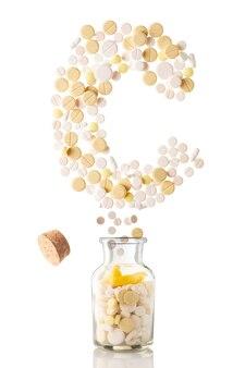 Różne pigułki wylatują ze szklanego słoika w formie litery c, odizolowanej na białym tle