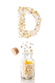 Różne pigułki wylatują ze szklanego słoika w formie litery d, odizolowanej na białym tle