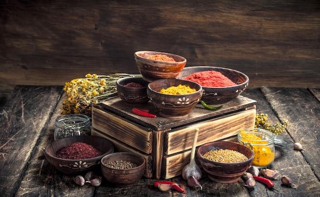 Różne pikantne przyprawy i zioła na drewnianym stole.