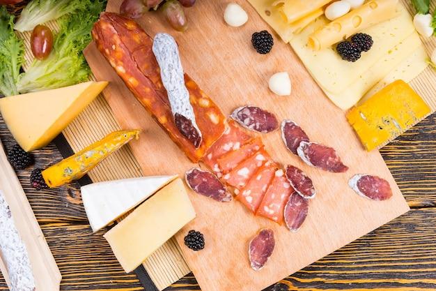 Różne pikantne wędliny z bukietem serów ułożone na stole bufetowym na drewnianej desce serów przyozdobionych jeżynami i oliwkami, widok z góry
