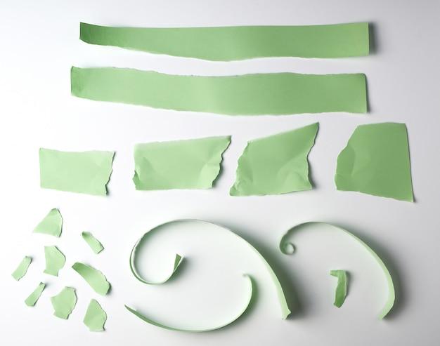 Różne podarte paski zielonego papieru na białym tle