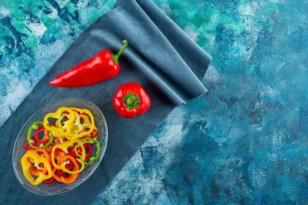 Różne pokrojone papryki w misce obok czerwonej papryki na kawałku tkaniny, na niebieskim tle.