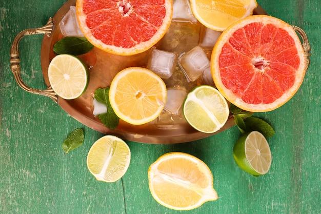 Różne pokrojone soczyste owoce cytrusowe z lodem na tacy na zielonym drewnianym stole