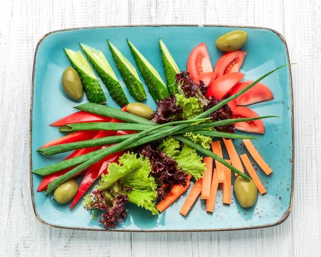 Różne pokrojone świeże warzywa na talerzu koloru