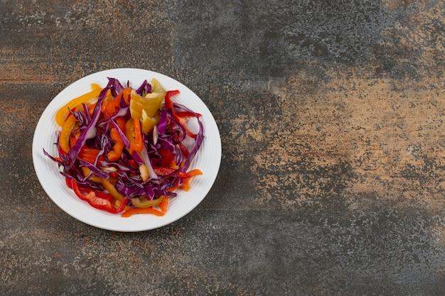 Różne pokrojone warzywa na białym talerzu.