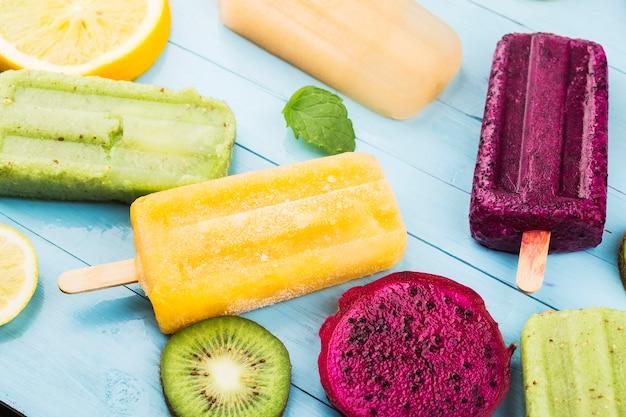 Różne popsicles owocowe są umieszczone na niebieskim tle drewnianej deski, popsicles kiwi, popsicles pomarańczowy, popsicles owoc smoka, popsicle kantalupa