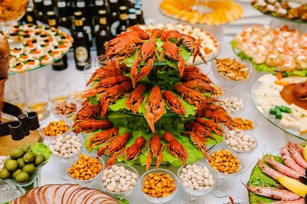 Różne potrawy gotowane na drewnianym stole raki, kalmary, owoce morza. alkohol i jedzenie. piwo z przekąskami na stole. koncepcja żywności w pomieszczeniu.