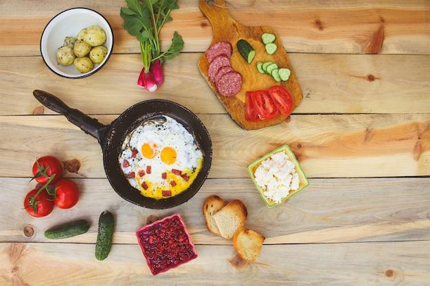 Różne potrawy: jajecznica na patelni, gotowane ziemniaki, twaróg, grzanki, rzodkiewki, ogórki, pomidory, wędzona kiełbasa, grzanki, mięta, szczaw na drewnianym stole