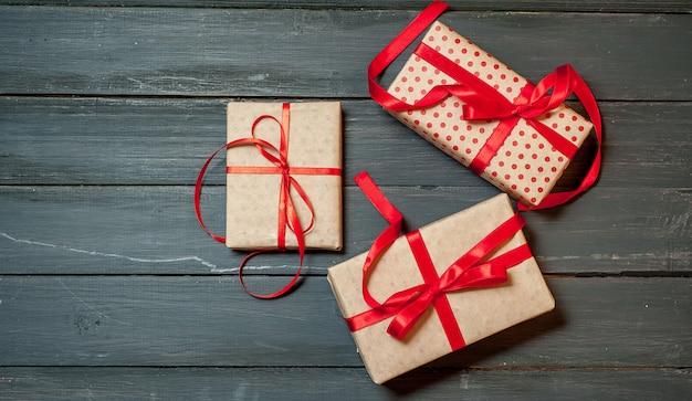 Różne prezenty z czerwoną wstążką na tle drewna