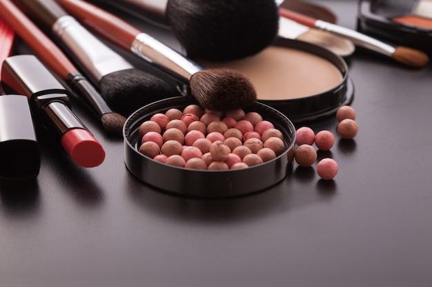 Różne produkty do makijażu na ciemnym czarnym tle z copyspace