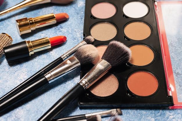 Różne produkty do makijażu, pędzle na niebiesko