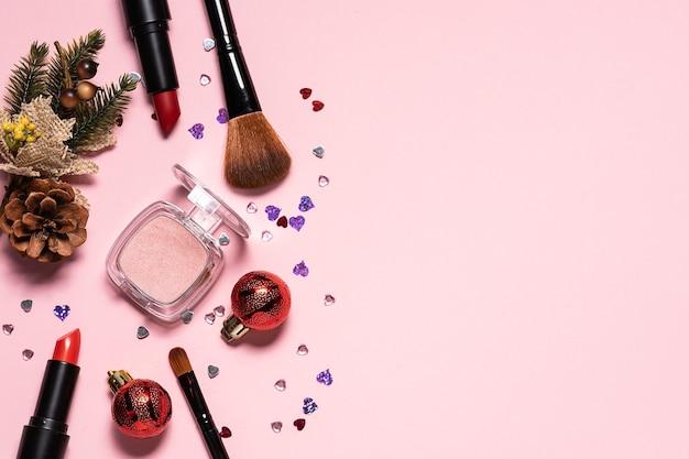 Różne produkty kosmetyczne i pędzle do makijażu z błyszczącym wystrojem świątecznym na różowym tle