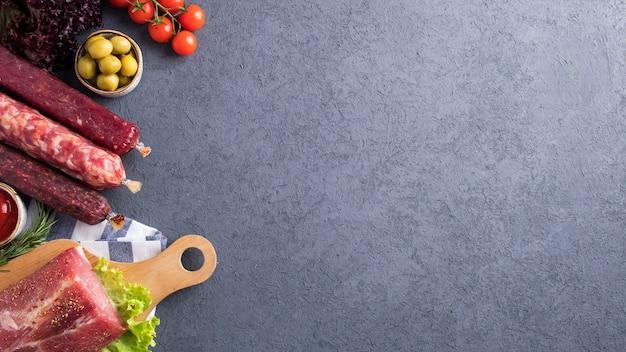 Różne produkty mięsne z warzywami i przyprawami. widok z góry.