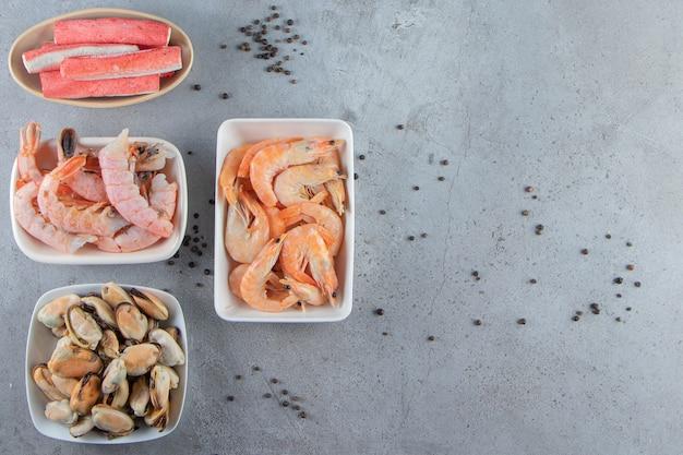 Różne produkty morskie w miskach, na marmurowym tle.