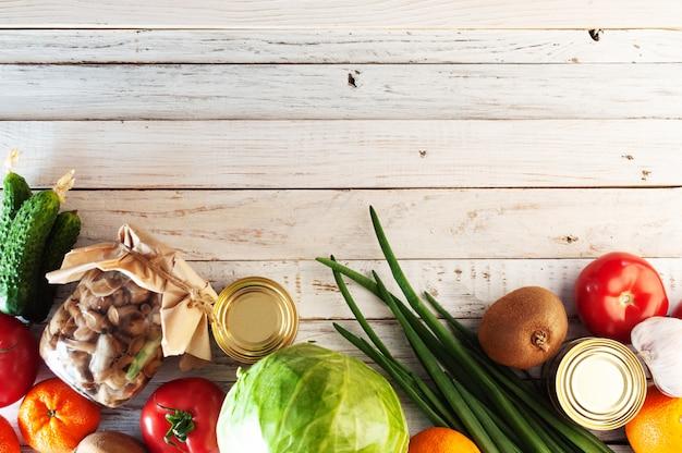 Różne produkty na białym drewnianym stole, układanie na płasko. miejsce na tekst. pojęcie kupowania żywności podczas kryzysu. widok z góry.