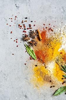 Różne proszki przyprawowe papryka curry kolendra imbir suszona cebula i czosnek kurkuma pieprz cynamon anyż i zioła rozmaryn liść laurowy na szarym tle kuchnia indyjska i azjatycka