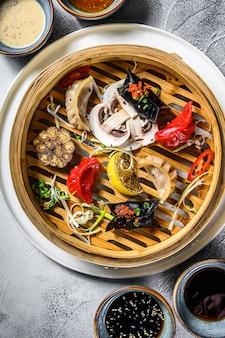 Różne przekąski dim sum w bambusowym parowcu. zestaw chińskich potraw. szare tło. widok z góry