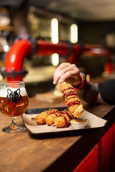 Różne przekąski do piwa fast food smażone paluszki serowe wędliny nuggetsy z kuflem piwa be