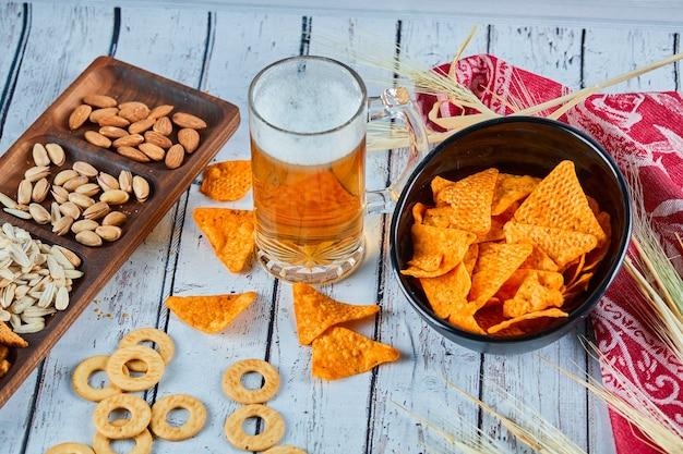 Różne przekąski, frytki i szklankę piwa na niebieskim stole.