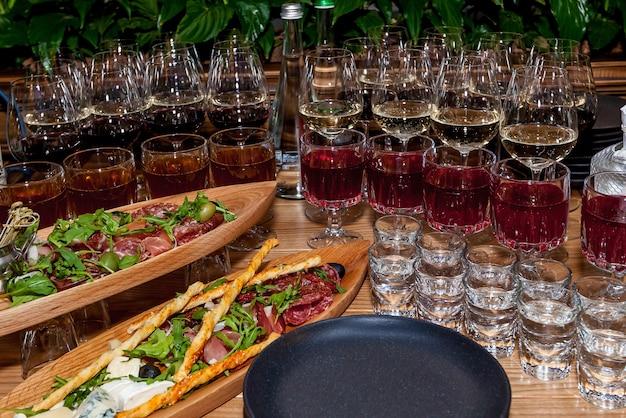 Różne przekąski i alkohol w szklankach na uroczystym stole do stołu bufetowego.
