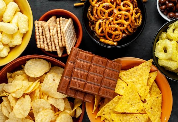 Różne przekąski i czekolada na czarnym stole