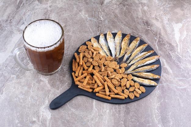 Różne przekąski i szklanka piwa na marmurowej powierzchni. zdjęcie wysokiej jakości
