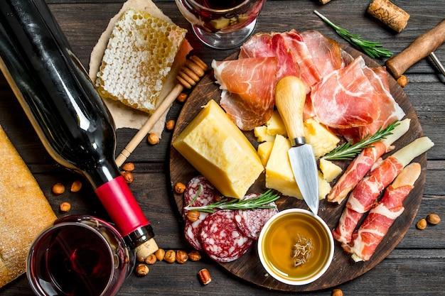Różne przekąski mięsne i serowe z czerwonym winem na rustykalnym stole.