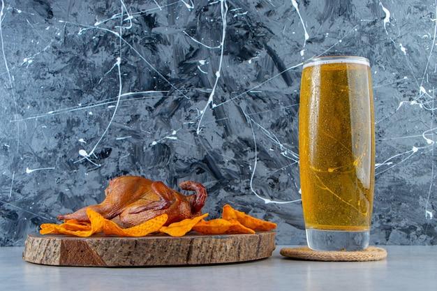 Różne przekąski na tablicy obok szklanki do piwa, na marmurowym tle.