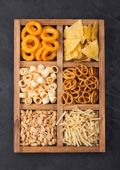Różne przekąski w vintage drewniane pudełko na tle czarnej kuchni. krążki cebulowe, nachosy, słone orzeszki ziemne z paluszkami ziemniaczanymi i precelkami. nadaje się do piwa i napojów gazowanych.
