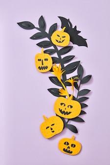 Różne przerażające dynie i nietoperz na gałęziach papieru pozostawia na fioletowym tle z miejsca na kopię. papier ręcznie robiony skład na halloween. płaskie ułożenie