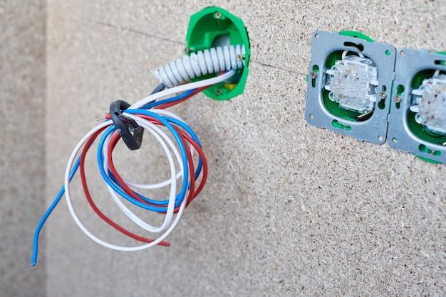 Różne przewody w gniazdku elektrycznym i przełączniki na ścianie