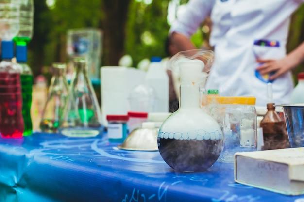 Różne przybory chemiczne na stole. z przodu znajduje się kolba, w której zachodzi reakcja chemiczna