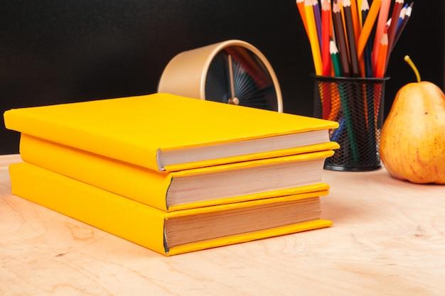 Różne przybory szkolne, książki i gruszka na drewnianym stole