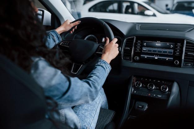 Różne przyciski i pokrętła. śliczna dziewczyna z czarnymi włosami próbuje swojego nowego drogiego samochodu w salonie samochodowym