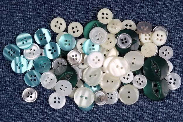 Różne przyciski z masy perłowej na niebieskim materiale, widok z góry