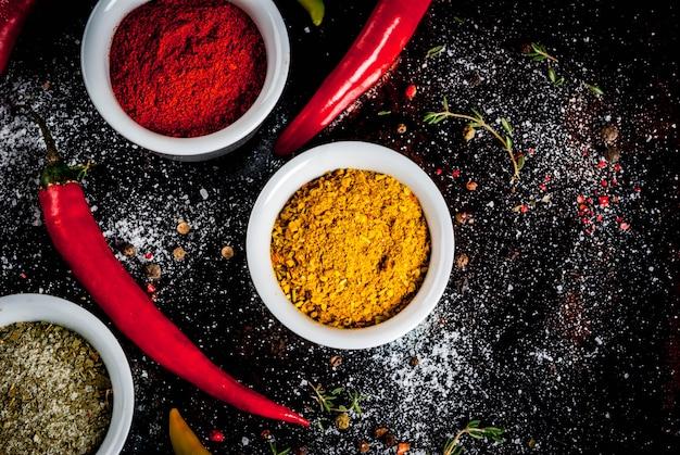 Różne przyprawy i przyprawy. gotowanie kurkuma, curry, papryka, pieprz, chili, suszona bazylia, sól, świeże chili, tymianek. czarny zardzewiały metal. widok z góry, .