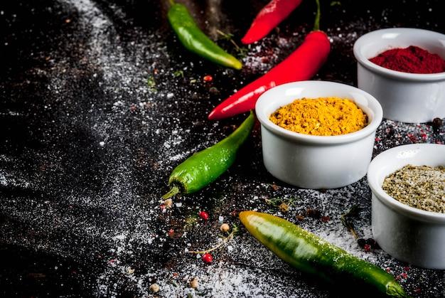 Różne przyprawy i przyprawy. gotowanie kurkuma, curry, papryka, pieprz, chili, suszona bazylia, sól, świeże chili, tymianek. czarny zardzewiały metal. .