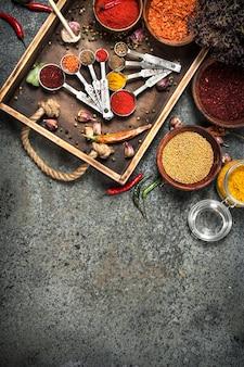 Różne przyprawy i zioła w drewnianej tacy na rustykalnym stole.