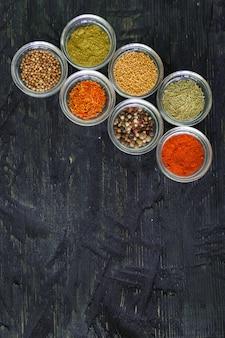 Różne przyprawy i zioła w przezroczystej misce na czarnym tle drewnianych, widok z góry z kopią tekstu.
