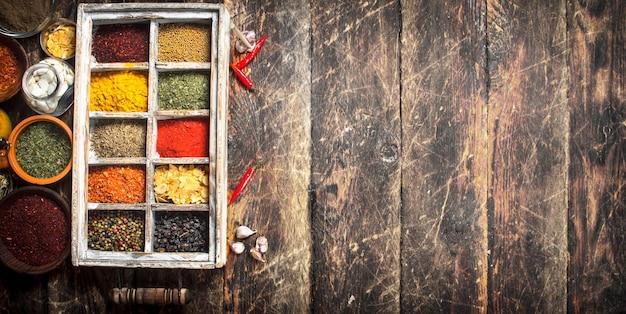 Różne przyprawy i zioła w pudełku na drewnianym stole.