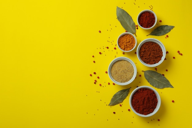 Różne przyprawy w białych miseczkach na żółtym tle