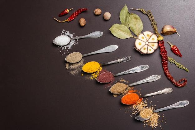 Różne przyprawy w łyżkach, suszone zioła i warzywa