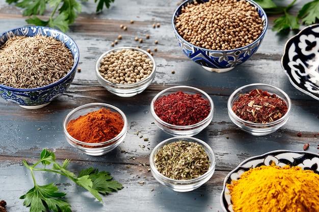 Różne przyprawy w miseczkach na szarym stole. papryka, kurkuma, czerwona papryka, kminek, kolendra. przyprawy w proszku